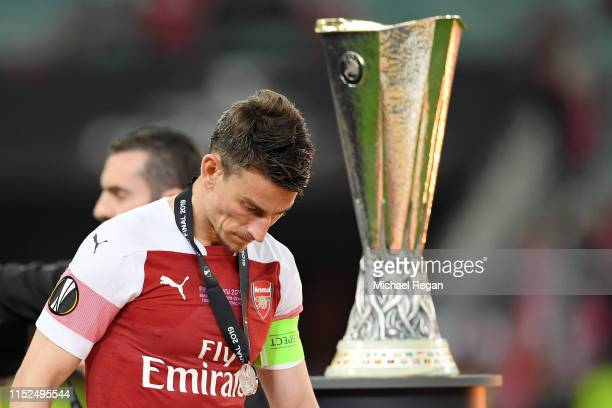 Laurent Koscielny of Arsenal looks dejected as he walks past the Europa League Trophy whilst coduring the UEFA Europa League Final between Chelsea...