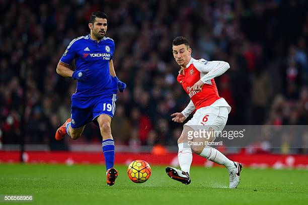Laurent Koscielny of Arsenal passes the ball under pressure from Diego Costa of Chelsea during the Barclays Premier League match between Arsenal and...