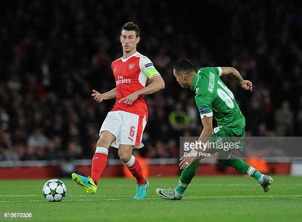 Laurent Koscielny of Arsenal passes under pressure from Marcelinho of Ludogorets during the UEFA Champions League match between Arsenal FC and PFC...
