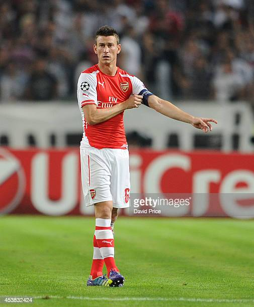 Laurent Koscielny of Arsenal pulls on the captains armband during the UEFA Champions League playoff first leg between Besiktas JK and Arsenal FC on...