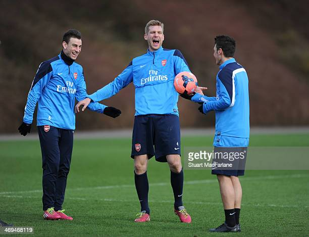 Laurent Koscielny, Per Mertesacker and Mesut Oezil of Arsenal share a joke during a training session at London Colney on February 15, 2014 in St...