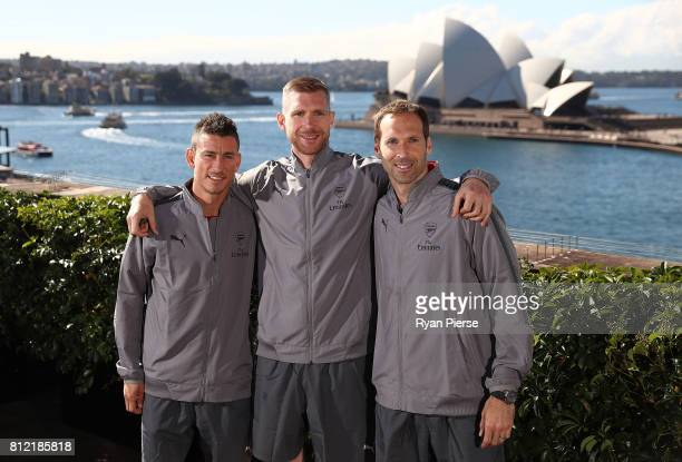 Laurent Koscielny Per Mertesacker and Petr Cech pose in front of the Sydney Opera House during an Official Welcome to Sydney for Arsenal FC at Museum...