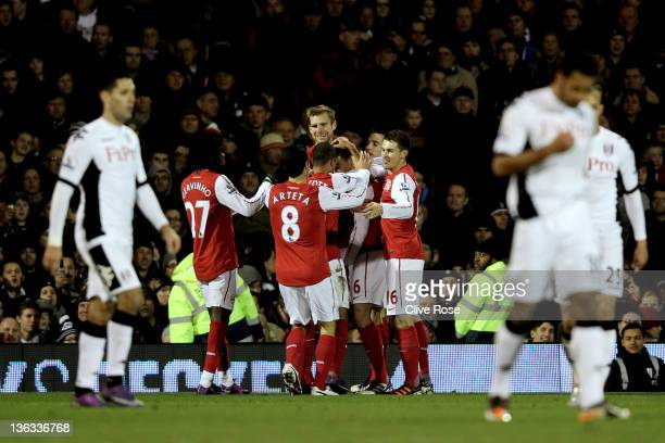 Laurent Koscielny#6 of Arsenal celebrates with teammates after scoring the opening goal during the Barclays Premier League match between Fulham and...
