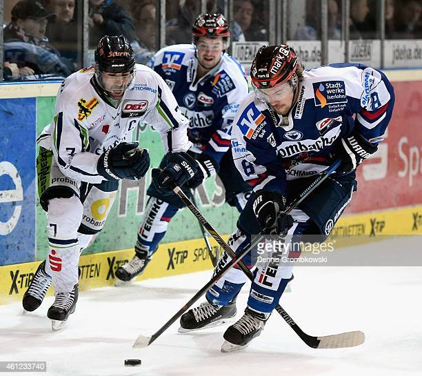 Laurent Meunier of Straubing Tigers challenges Nicholas Petersen of Iserlohn Roosters during the DEL Ice Hockey game between Iserlohn Roosters and...