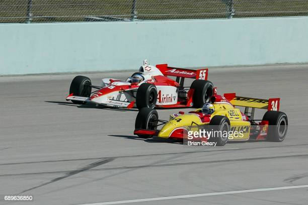 Laurent Redon of France drives the Dallara/Infiniti on the track next to Rick Treadway in the G Force/Chevrolet during the 20th Anniversary Grand...