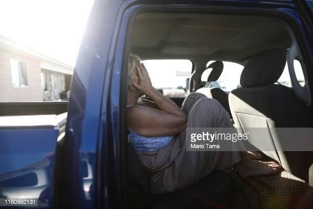 Laurette Eldridge pauses after waking up in the truck where she slept outside her parents' home which has been deemed uninhabitable due to structural...