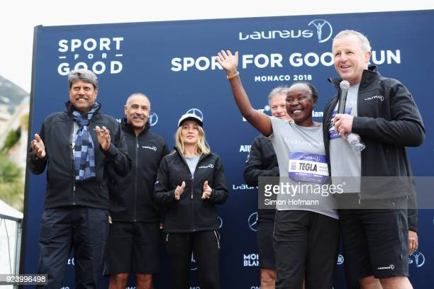 Laureus Academy Chairman Sean Fitzpatrick speaks as Laureus Academy Member Tegla Loroupe waves with other Laureus Academy members Kapil DevDaley...
