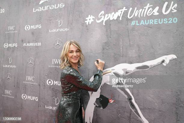 Laureus Academy member Nadia Comaneci signs the backdrop during her arrival at the 2020 Laureus World Sports Awards at Verti Music Hall on February...