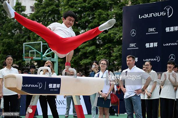Laureus Academy Member Russian gymnast Alexei Nemov instructs students in vaulting horse exercise during a physical education class at Gezhi Middle...