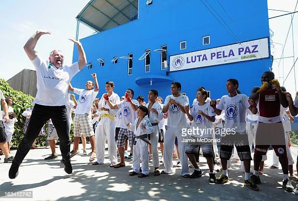 Laureus Academy member Sean Fitzpatrick demonstrates the 'Haka' the traditional New Zealand Maori war dance to local children during the Luta Pela...