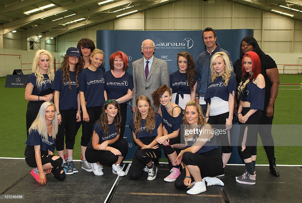 Laureus Academy Member Sir Bobby Charlton and Laureus Ambassador Michael Vaughan stand for a picture with a group of street dancers during their visit to the Laureus Urban Stars project launch at The Cliff Training Ground on August 16, 2011 in Manchester, England.