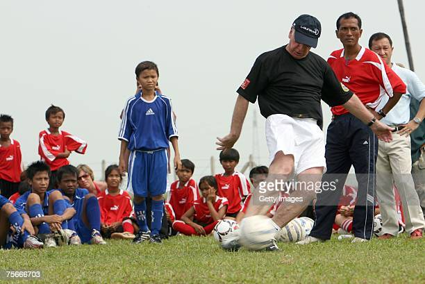 Laureus World Sports Academy member Bobby Charlton takes part in a training session with the Spirit of Soccer project founder Scotty Lee and children...