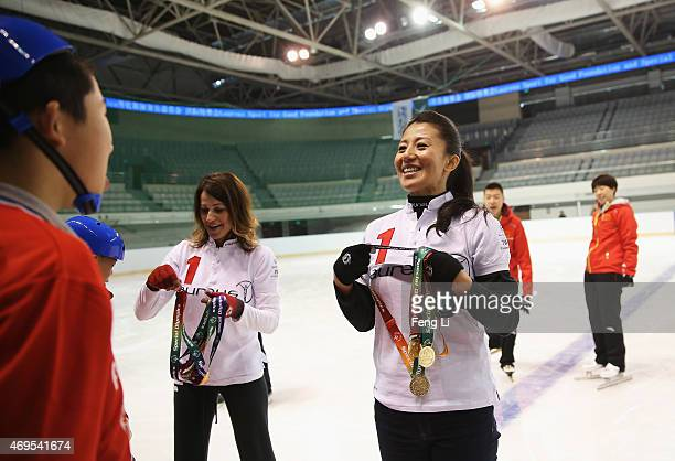 Laureus World Sports Academy member Yang Yang and Nadia Comaneci gives a child a medal during a visit to a Laureus Sport For Good Project prior to...
