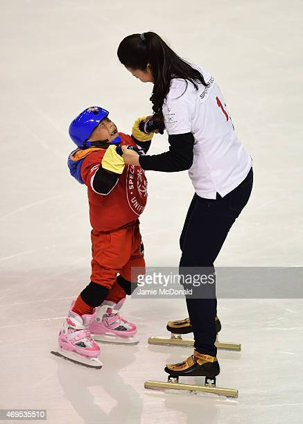 Laureus World Sports Academy member Yang Yang of China helps a young child as she visits a Laureus Sport For Good Project prior to the Laureus World...