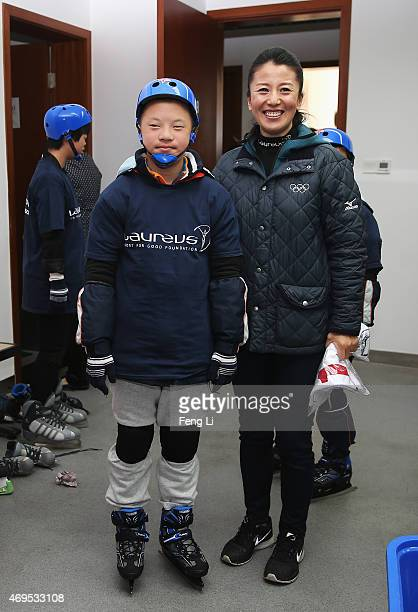 Laureus World Sports Academy member Yang Yang of China poses with a young boy as she visits a Laureus Sport For Good Project prior to the Laureus...