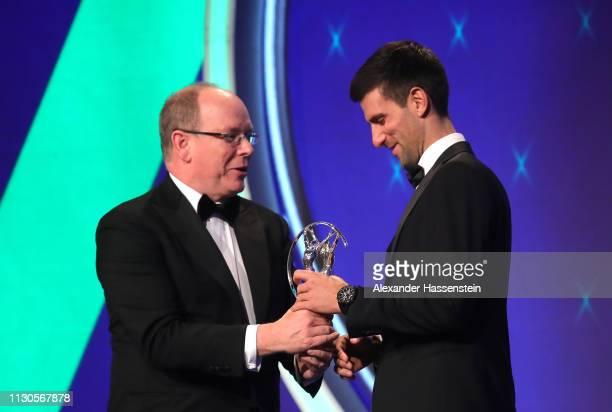 Laureus World Sportsman of The Year 2019 winner Novak Djokovic accepts his Laureus award on stage from Albert II Prince of Monaco during the 2019...