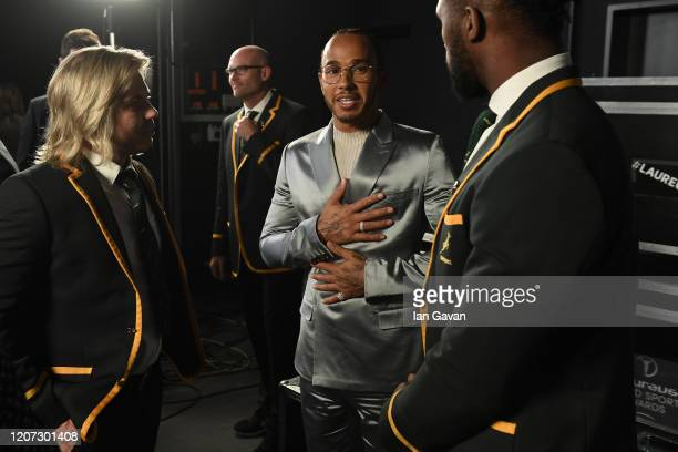 Laureus World Sportsman of the Year winner Lewis Hamilton speaks with Faf de Klerk and Captain Siya Kolisi of the South African Rugby Union team...