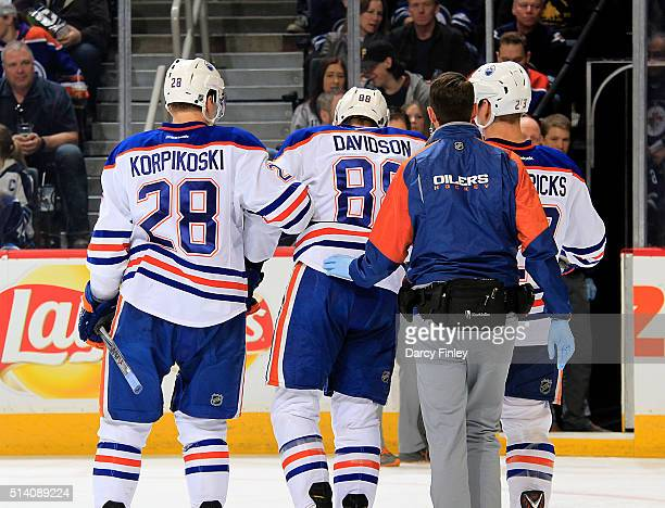Lauri Korpikoski and Matt Hendricks of the Edmonton Oilers help teammate Brandon Davidson off the ice after suffering an injury during first period...