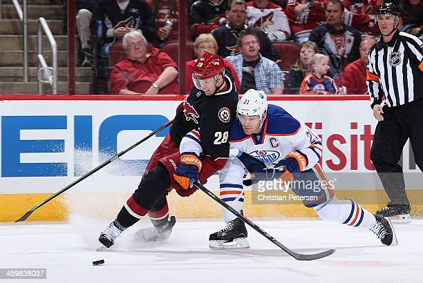 Lauri Korpikoski of the Phoenix Coyotes and Andrew Ference of the Edmonton Oilers battle for a loose puck during the first period of the NHL game at...