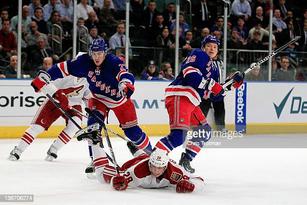 Lauri Korpikoski of the Phoenix Coyotes falls to the ice after a challenge from Ryan McDonagh of the New York Rangers and Ruslan Fedotenko of the New...