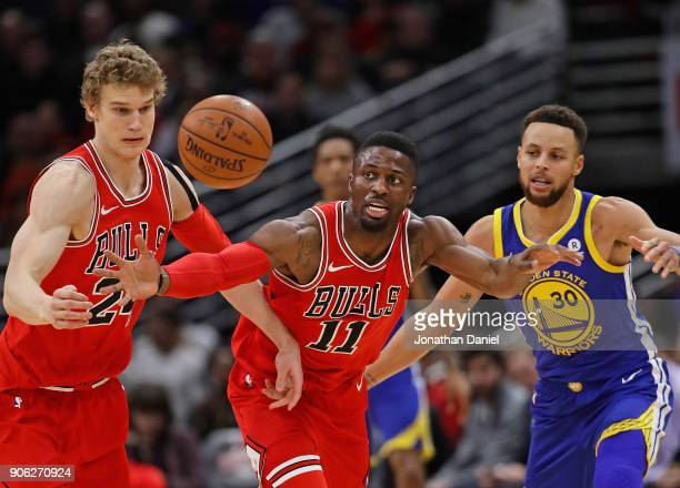 Lauri Markkanen and David Nwaba of the Chicago Bulls chase down a loose ball in front of Stephen Curry of the Golden State Warriors at the United...