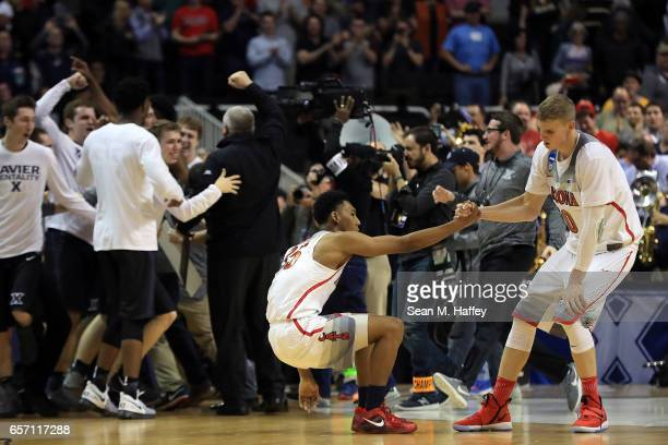 Lauri Markkanen helps up Allonzo Trier of the Arizona Wildcats after their team lost to the Xavier Musketeers during the 2017 NCAA Men's Basketball...