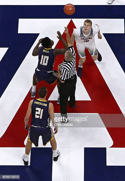 Lauri Markkanen of the Arizona Wildcats and Ibrahim Sylla of the Northern Colorado Bears line up for the opening tip during the first half of the...