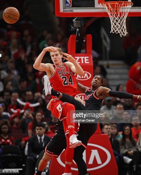 Lauri Markkanen of the Chicago Bulls and Josh Richardson of the Miami Heat get tanglesd up going for a rebound at the United Center on November 26...