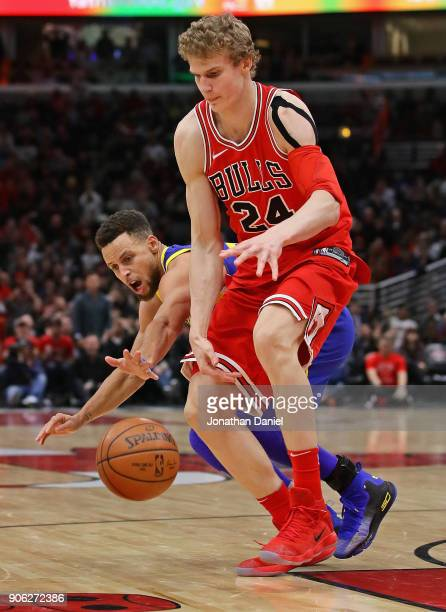 Lauri Markkanen of the Chicago Bulls and Stephen Curry of the Golden State Warriors chase a loose ball at the United Center on January 17 2018 in...