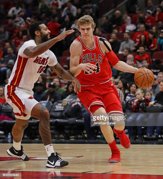Lauri Markkanen of the Chicago Bulls drives against James Johnson of the Miami Heat at the United Center on January 15 2018 in Chicago Illinois The...