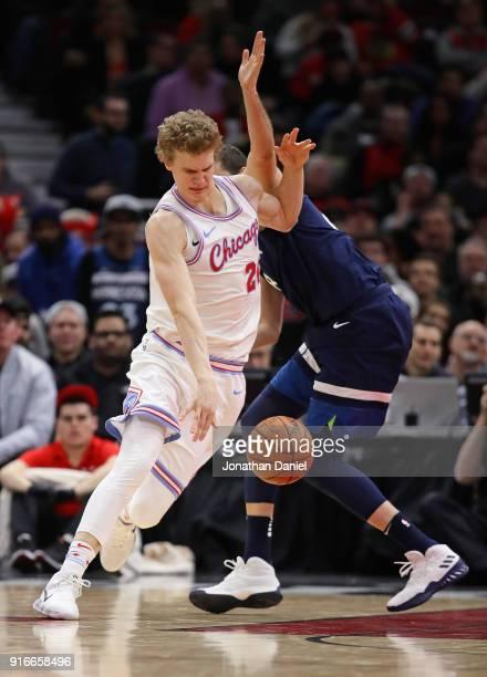 Lauri Markkanen of the Chicago Bulls drives around Nemanja Bjelica of the Minnesota Timberwolves at the United Center on February 9 2018 in Chicago...