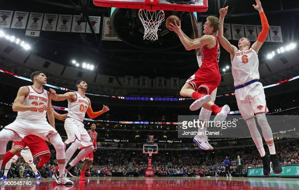 Lauri Markkanen of the Chicago Bulls drives to the basket between Kristaps Porzingis and Frank Ntilikina of the New York Knicks at the United Center...