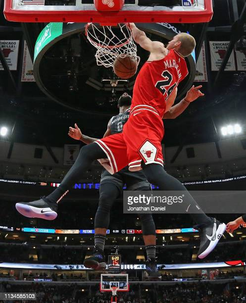 Lauri Markkanen of the Chicago Bulls dunks over Andre Drummond of the Detroit Pistons at the United Center on March 08 2019 in Chicago Illinois The...