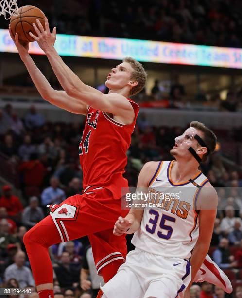 Lauri Markkanen of the Chicago Bulls goes up for a shot over Dragan Bender of the Phoenix Suns at the United Center on November 28 2017 in Chicago...