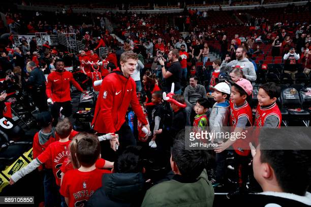 Lauri Markkanen of the Chicago Bulls high fives fans before the game against the New York Knicks on December 9 2017 at the United Center in Chicago...
