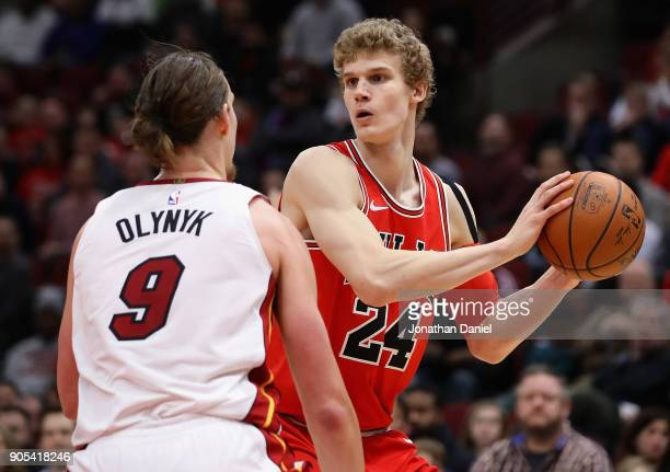 Lauri Markkanen of the Chicago Bulls looks to pass against Kelly Olynyk of the Miami Heat at the United Center on January 15 2018 in Chicago Illinois...