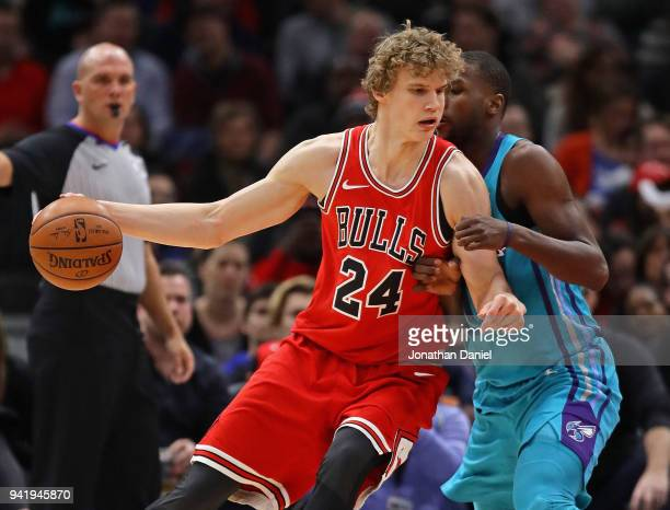 Lauri Markkanen of the Chicago Bulls moves against Michael KiddGilchrist of the Charlotte Hornets at the United Center on April 3 2018 in Chicago...