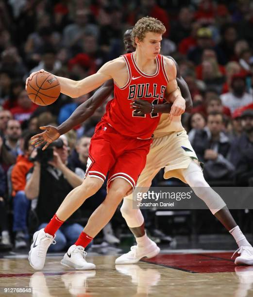 Lauri Markkanen of the Chicago Bulls moves against Thon Maker of the Milwaukee Bucks at the United Center on January 28 2018 in Chicago Illinois The...