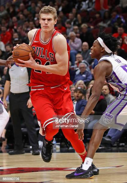 Lauri Markkanen of the Chicago Bulls moves past De'Aaron Fox of the Sacramento Kings at the United Center on December 1 2017 in Chicago Illinois The...