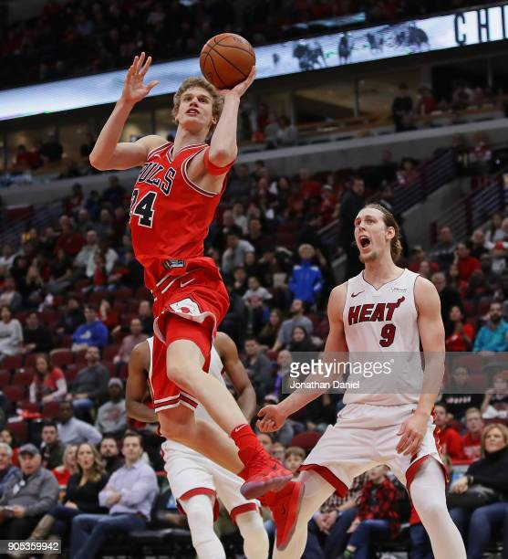 Lauri Markkanen of the Chicago Bulls puts up a shot past Kelly Olynyk of the Miami Heat at the United Center on January 15 2018 in Chicago Illinois...