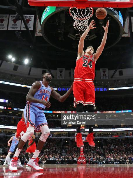 Lauri Markkanen of the Chicago Bulls rebounds over Dewayne Dedmon of the Atlanta Hawks at the United Center on March 03 2019 in Chicago Illinois The...