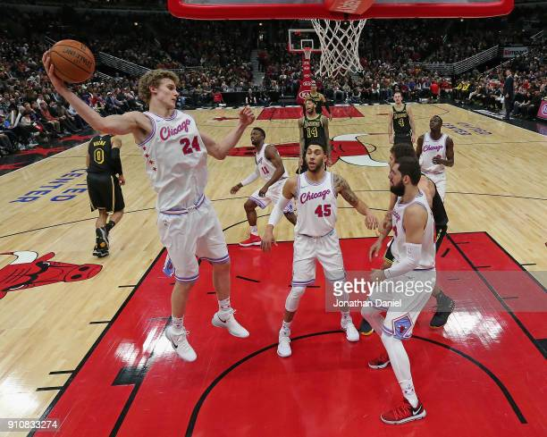 Lauri Markkanen of the Chicago Bulls rebounds over teammates Denzel Valentine and Nikola Mirotic during a game against the Los Angeles Lakers at the...