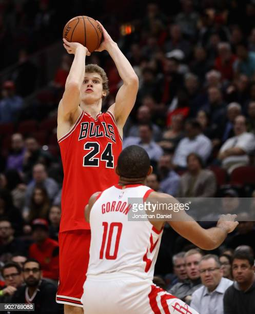 Lauri Markkanen of the Chicago Bulls shoots over Eric Gordon of the Houston Rockets at the United Center on January 8 2018 in Chicago Illinois The...