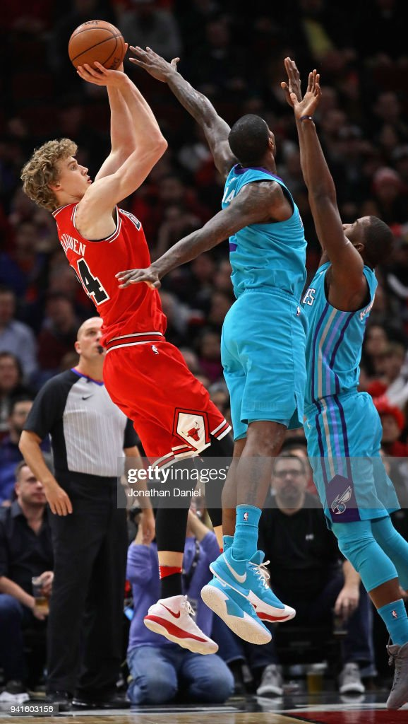 Lauri Markkanen #24 of the Chicago Bulls shoots over Michael Kidd-Gilchrist #14 (R) and Marvin Williams #2 of the Charlotte Hornets at the United Center on April 3, 2018 in Chicago, Illinois.