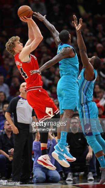 Lauri Markkanen of the Chicago Bulls shoots over Michael KiddGilchrist and Marvin Williams of the Charlotte Hornets at the United Center on April 3...