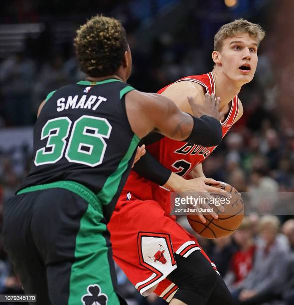 Lauri Markkanen of the Chicago Bulls tries to get past Marcus Smart of the Boston Celtics at United Center on December 08 2018 in Chicago Illinois...
