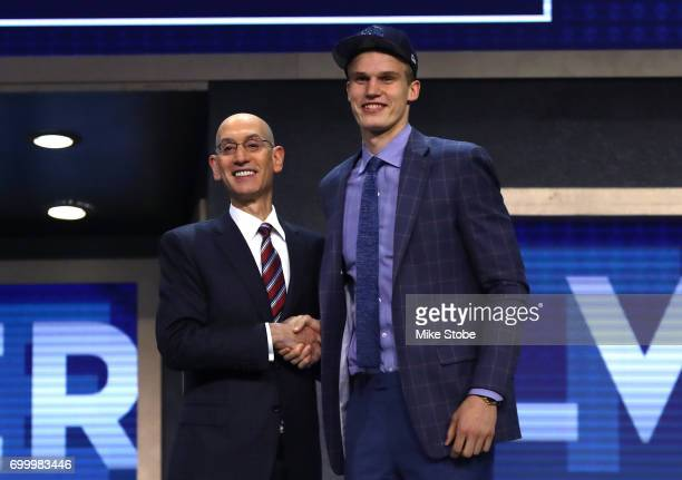 Lauri Markkanen walks on stage with NBA commissioner Adam Silver after being drafted seventh overall by the Minnesota Timberwolves during the first...