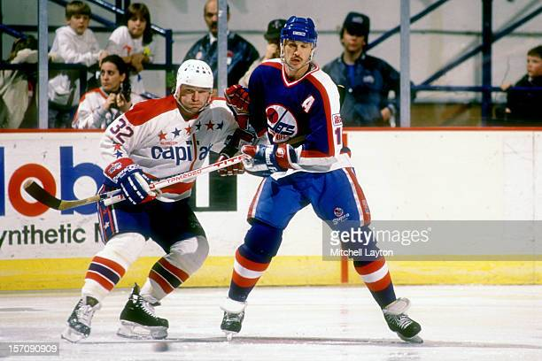 Laurie Boschman of the Winnipeg Jets and Dale Hunter of the Washington Capitals fight for position during a hockey game on January 23 1990 at Capital...