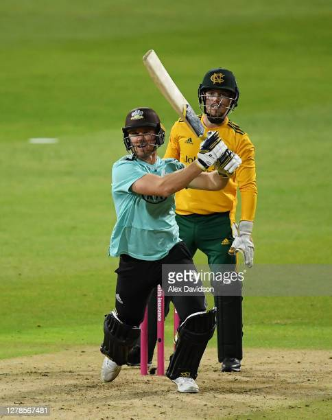 Laurie Evans of Surrey hits runs watched on by Tom Moores of Notts Outlaws during the Vitality Blast 20 Final between Surrey and Notts Outlaws at...