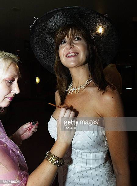 Laurie Faulkner applies a fake tattoo to Gena Conomos from Brisbane at the Crown Oaks Ladies Luncheon on 2nd November 2005 THE AGE NEWS Picture by...